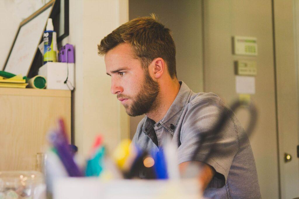 مساعد اداري ينظر الى شاشة الحاسوب اثناء ممارسته الى مهنته